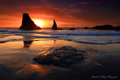 Sunset and Sun Star with the Wizards Hat Sea Stack in the Surf From Face Rock Beach in Bandon Oregon