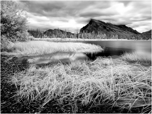 Black and White Photo of a Lake with a Mountain in the Backround