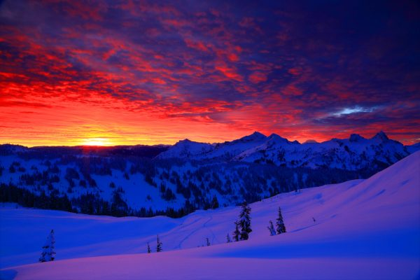 Photo of a Red Sunrise over a Snowy Mountain